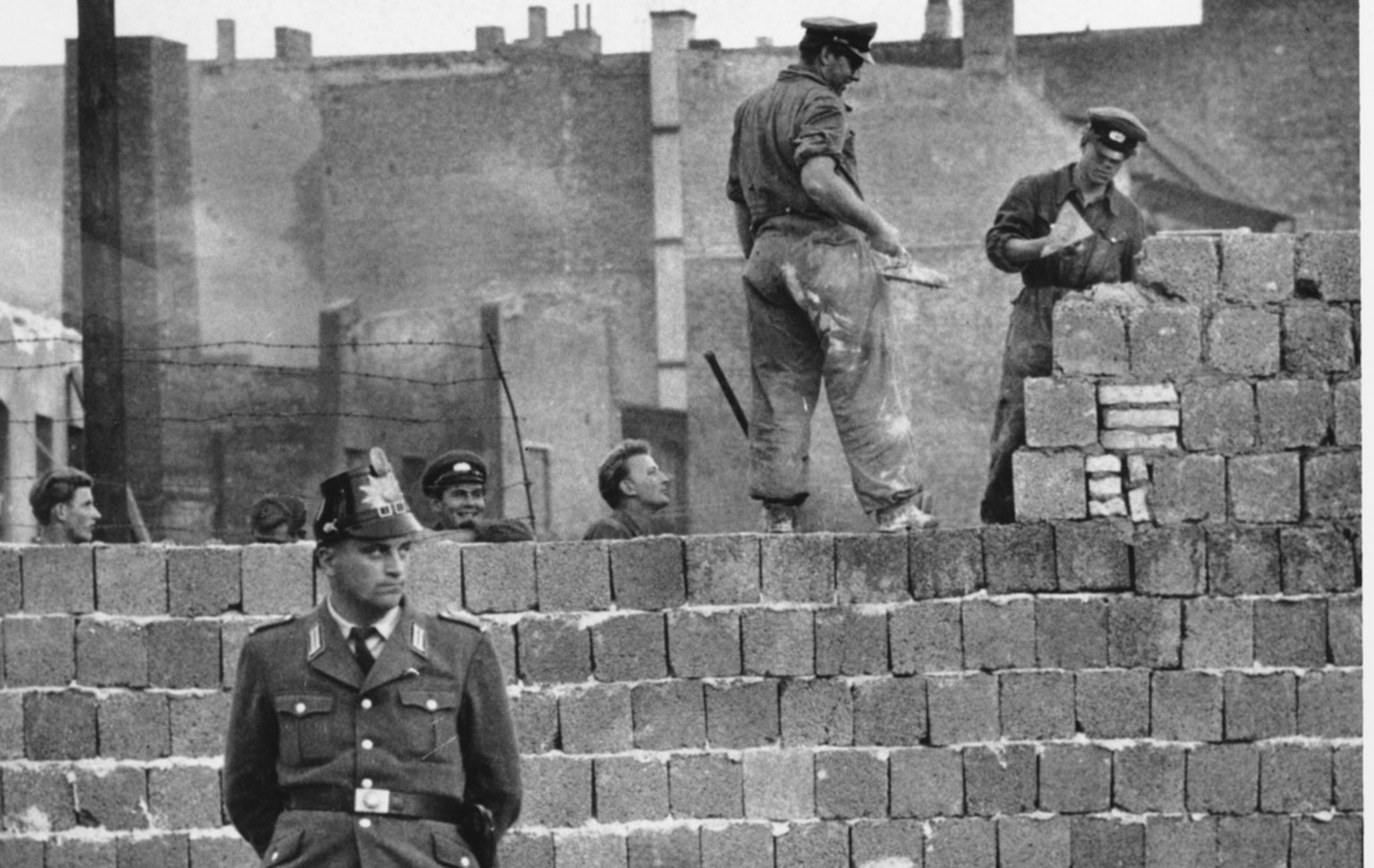 A West Berlin guard stands in front of the concrete wall dividing East and West Berlin at Bernauer Strasse as East Berlin workmen add blocks to the wall to increase the height of the barrier, Oct. 7, 1961. Berlin on Wednesday, Aug. 13, 2008 sees the 47th anniversary of the beginning of the erection of the so-called Berlin Wall.  (AP Photo)