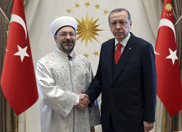Turkey's President Recep Tayyip Erdogan, right, shakes hands with Ali Erbas, Chief of Religious Affairs, at his palace in Ankara, Turkey, Wednesday, Sept. 27, 2017. Erdogan's office has confirmed that he will meet with Russia's President Vladimir Putin in Ankara on Thursday to discuss bilateral issues, Iraq and Syria.(Pool photo via AP)