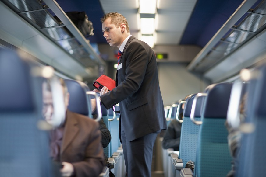 ARCHIVBILD ZUR VERGABE DER FERNVERKEHRSKONZESSIONEN DURCH DAS BAV, AM MONTAG, 23. OKTOBER 2017 - A ticket collector checks the passengers' tickets in an InterCity train of the Swiss Federal Railways SBB circulating between Berne and Biel, Switzerland, on November 27, 2009. (KEYSTONE/Gaetan Bally) 