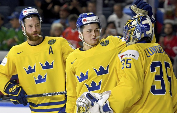 From left: Sweden's Victor Hedman and William Nylander thank goalkeeper Henrik Lundqvist at the end  of a group A match of the 2017 Hockey World Championships between Sweden and Slovakia  in Lanxess Arena in Cologne, Germany, Tuesday, May 16, 2017.  (Monika Skolimowska/dpa via AP)