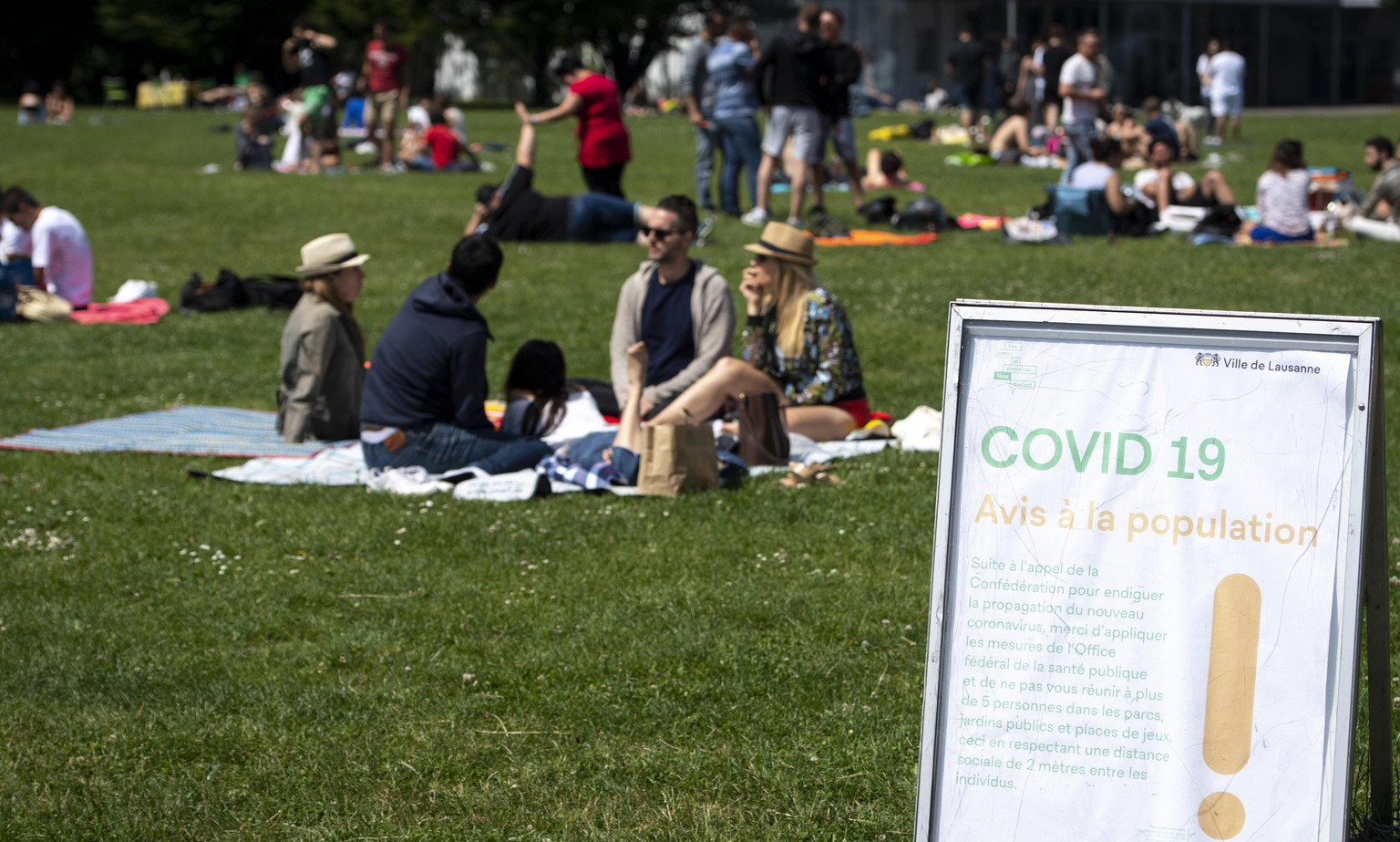 People enjoy the warm spring weather on the shore of the Lake Geneva during the state of emergency of the coronavirus disease (COVID-19) outbreak, in Lausanne, Switzerland, Sunday, May 24, 2020. In Switzerland from 11 May, loosening measures slowing down the ongoing pandemic of the COVID-19 disease, which is caused by the SARS-CoV-2 coronavirus, become effective by step. Classroom teaching at primary and lower secondary schools will again be permitted. Shops, markets, museums, libraries and restaurants will be able to reopen under strict compliance with precautionary measures. (KEYSTONE/Laurent Gillieron).
