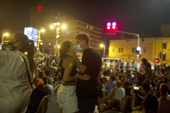 A couple kisses while wearing face masks to curb the spread of the coronavirus during a protest against Israel's Prime Minister Benjamin Netanyahu outside his residence in Jerusalem, Tuesday, Aug. 4, 2020. Ongoing protests are calling for the embattled Israeli leader to resign as he faces a trial on corruption charges and grapples with a deepening coronavirus crisis. (AP Photo/Maya Alleruzzo)