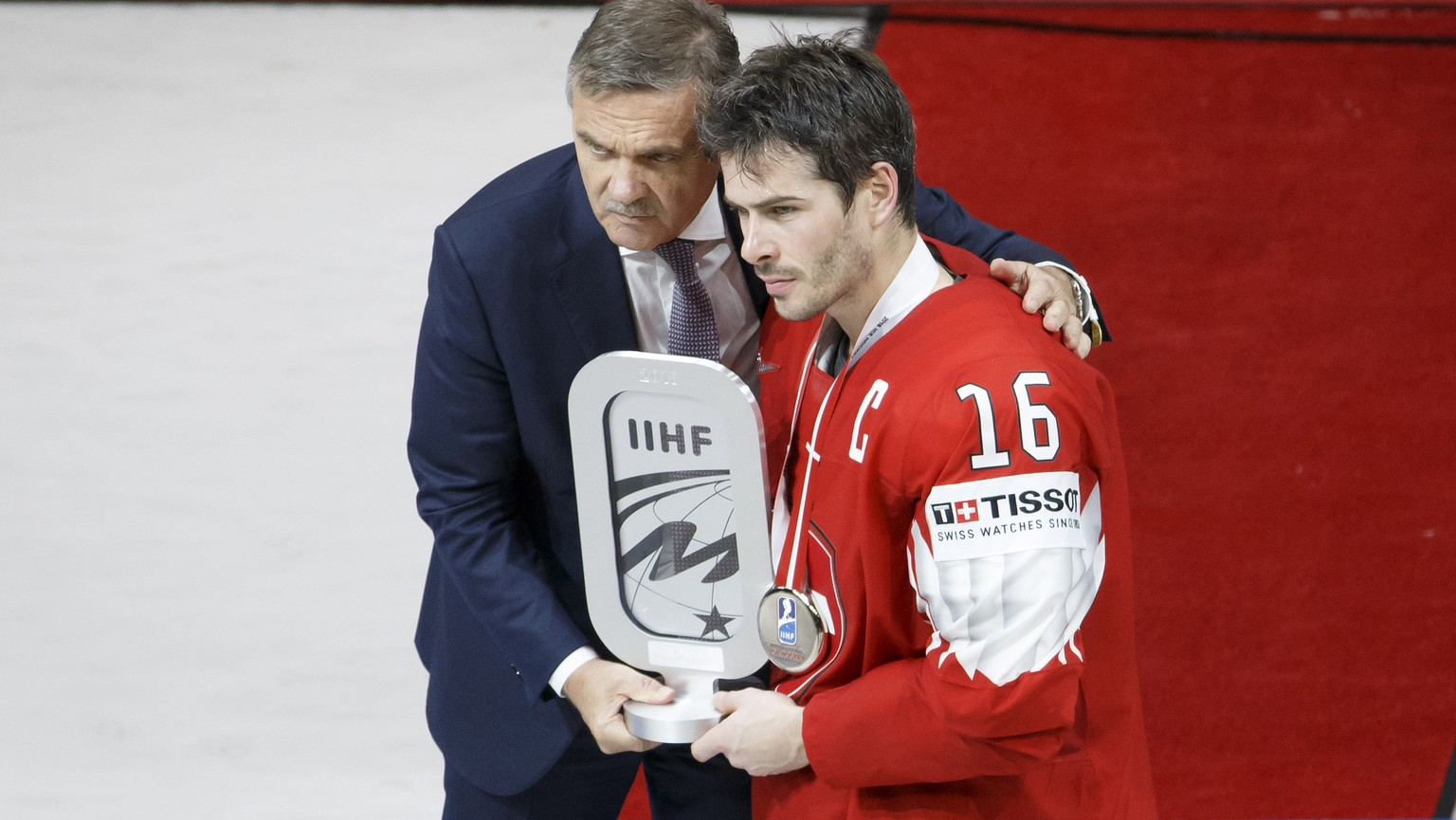 Rene Fasel, left, President of IIHF, gives the silver trophy to Switzerland's defender Raphael Diaz, right, after team Switzerland losing agains team Sweden, during the shootout of the IIHF 2018 World Championship Gold Medal game between Sweden and Switzerland, at the Royal Arena, in Copenhagen, Denmark, Sunday, May 20, 2018. (KEYSTONE/Salvatore Di Nolfi)