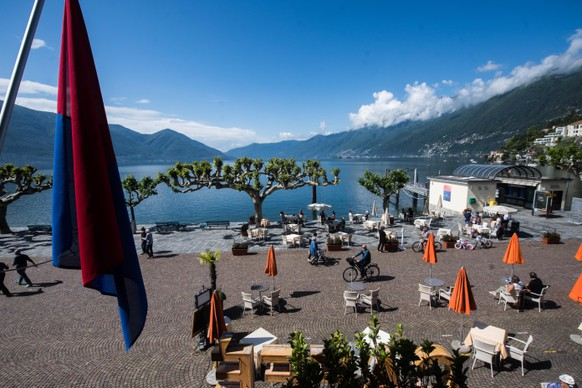 epa08427464 Locals and tourists alike enjoy the sunny weather on the shores of Lake Maggiore in Ascona, Switzerland, 17 May 2020. Tourism is returning to the Italian-speaking canton of Ticino as Switzerland begins to ease some of the movement restrictions imposed in a bid to slow down the spread of the pandemic COVID-19 disease caused by the SARS-CoV-2 coronavirus.  EPA/SAMUEL GOLAY