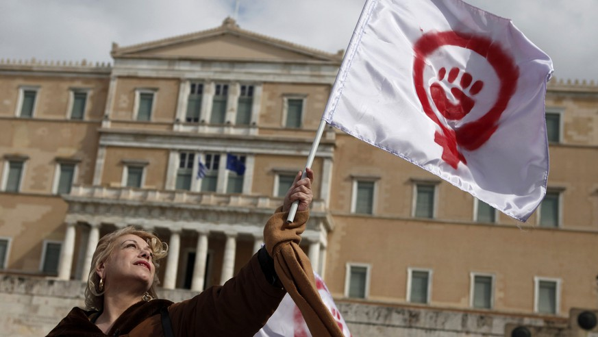 A woman waves a flag depicting a symbol of feminism during a march to celebrate International Women's Day in Athens March 8, 2014. On March 8 activists around the globe celebrate International Women's Day, which dates back to the beginning of the 20th Century and has been observed by the United Nations since 1975. The UN writes that it is an occasion to commemorate achievements in women's rights and to call for further change. REUTERS/Alkis Konstantinidis (GREECE - Tags: CIVIL UNREST)
