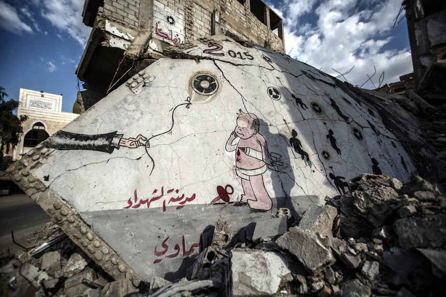 epa05507071 A picture made available on 22 August 2016 showing a graffiti in memory of the chemical attack victims, Zamalka, outskirts of Damascus, Syria, 21 August 2016. On 21 August 2013 Ghouta was bombed by Sarin, a chemical agent that affects the nervous system and prohibited by the Chemical Weapons Convention (CWC) as a weapon of mass destruction. The number of casualties is unknown with most reports indicating an average of 1400 death. The bombing was condemed by the Arab League, the European Union, and the United States, with a UN investigation team reporting that the nature, quality, and quantity of agents used in the attack idicate that the perpetrators had access to the chemical weapons stockpile of the Syrian military, and the expertise to arm them. The Syrian government accepted a US-Russia negotiated deal to turn over its chemical weapons stockpiles for destruction, and declated its intention to join the CWC.  EPA/MOHAMMED BADRA