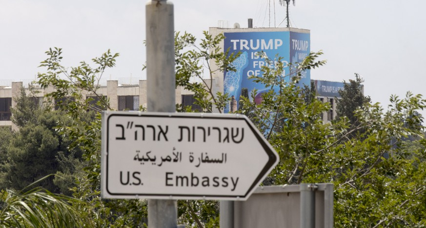 epa06735284 A road sign direction to the US embassy visible next to a banner reading 'Trump is a friend of Zion', displayed next to the US embassy, ahead of events marking the embassy inauguration in Jerusalem in Jerusalem, 14 May 2018. US President Donald J. Trump's administration will officially transfer the ambassador's offices to the consulate building and temporarily use it as the new US Embassy in Jerusalem as of 14 May 2018. Trump in December last year recognized Jerusalem as Israel's capital and announced an embassy move from Tel Aviv, prompting protests in the occupied Palestinian territories and several Muslim-majority countries.  EPA/ATEF SAFADI