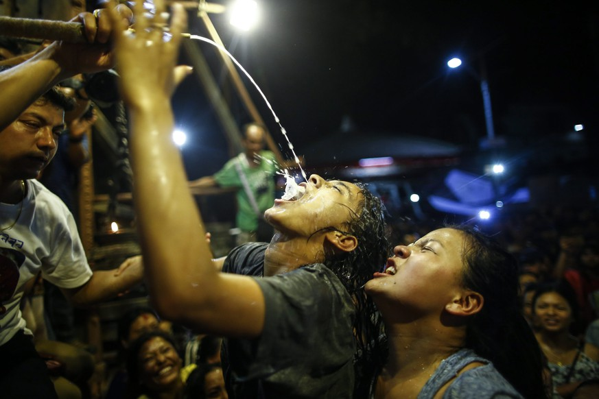 epa05544818 Nepalese women and young girls struggle to drink homemade alcohol poured through a pipe sticking out of the mouth of Swet Bhairab, a god of Power, during the Indra Jatra festival at Basantapur Durbar Square in Kathmandu, Nepal, 17 September 2016. Hundreds of women and young girls gathered to drink alcohol as a blessing from idol of Swet Bhairab which they believes will keep them free from all diseases. The Indra Jatra festival is celebrated to honor Indra, the king of gods and god of rains. The festival also marks the end of the monsoon.  EPA/NARENDRA SHRESTHA