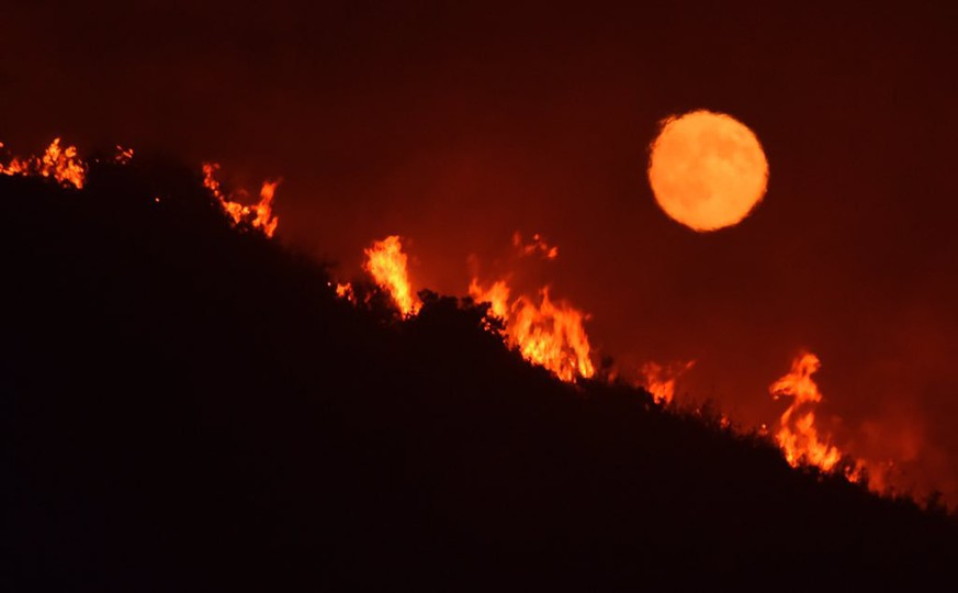 This Saturday, July 8, 2017, photo released by the Santa Barbara County Fire Department shows the moon rising over flames on a hilltop near Highway 166 east of Santa Maria, Calif., in what is known as the Alamo Fire in Santa Barbara County, Calif. Wildfires barreled across the baking landscape of the western U.S. and Canada, destroying a smattering of homes, forcing thousands to flee and temporarily trapping children and counselors at a California campground. (Mike Eliason/Santa Barbara County Fire Department via AP)