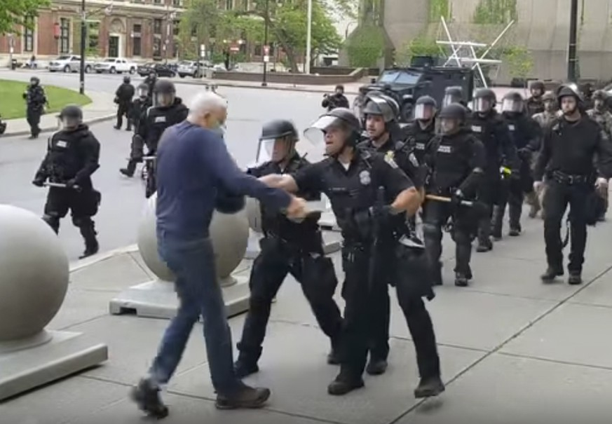 In this image from video provided by WBFO, a Buffalo police officer appears to shove a man who walked up to police Thursday, June 4, 2020, in Buffalo, N.Y. Video from WBFO shows the man appearing to hit his head on the pavement, with blood leaking out as officers walk past to clear Niagara Square. Buffalo police initially said in a statement that a person