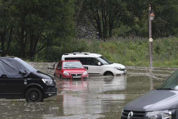 cars are trapped in a flooded street near the road of the nineteenth stage of the Tour de France cycling race over 126,5 kilometers (78,60 miles) with start in Saint Jean De Maurienne and finish in Tignes, France, Friday, July 26, 2019. Organizers stopped the world's premier cycling event Friday for the riders' safety when a sudden, violent storm made the route through the Alps too dangerous. (AP Photo/Thibault Camus)