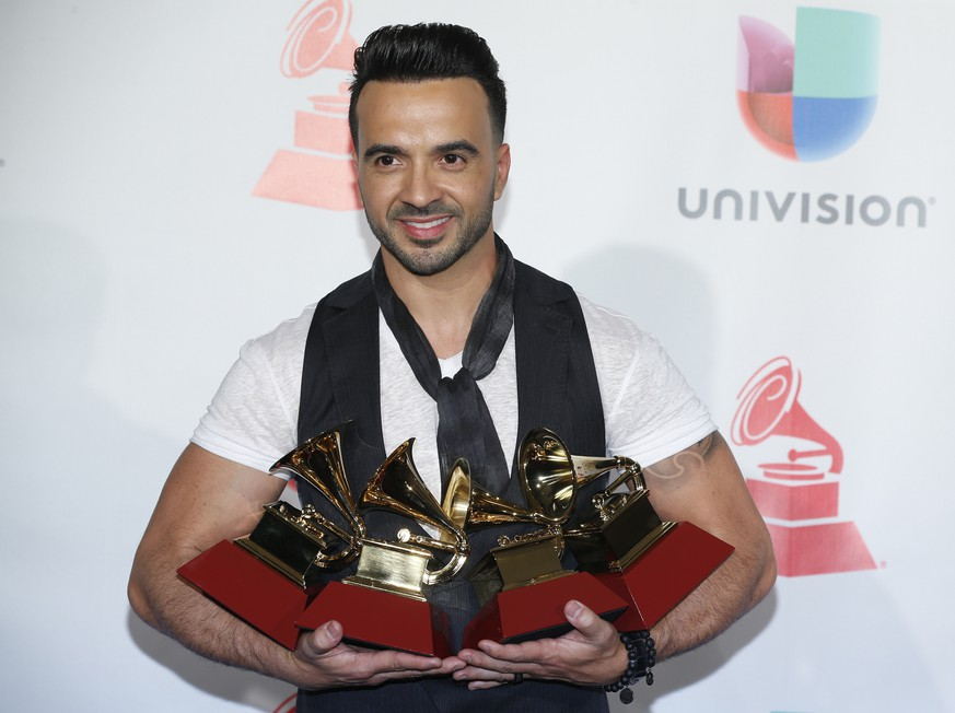 Luis Fonsi poses in the press room with the awards for best urban/fusion/performance, best short form music video, record of the year, and song of the year for