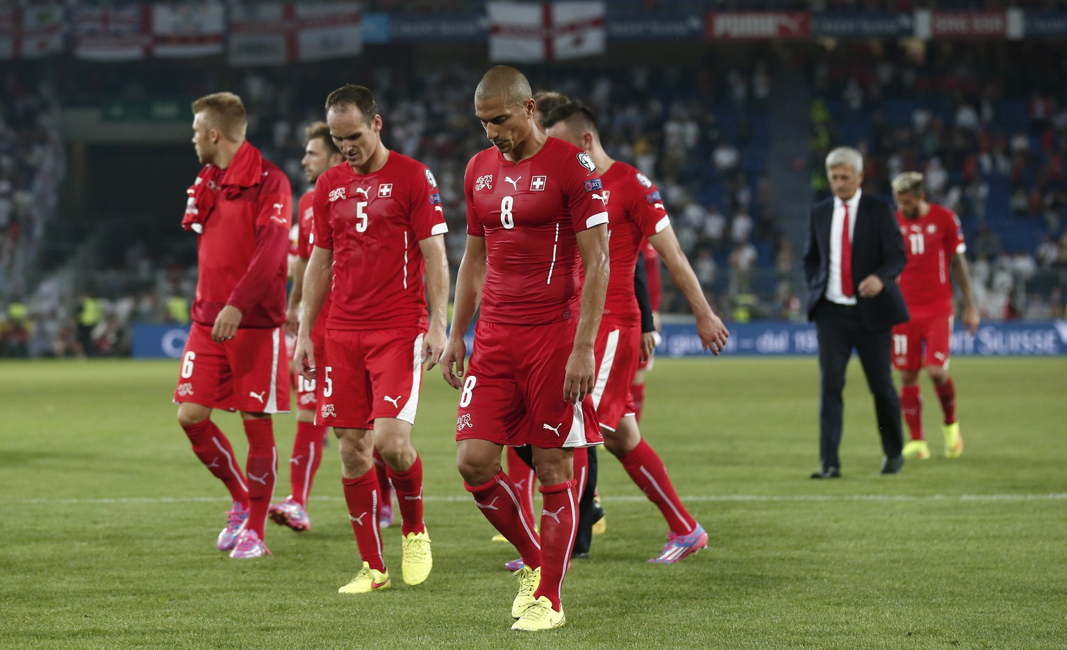 Swiss midfielder Goekhan Inler, front, and his teammates leave the pitch after the UEFA EURO 2016 qualifying match Switzerland against England at the St. Jakob-Park stadium in Basel, Switzerland, Monday, September 8, 2014. (KEYSTONE/Peter Klaunzer)