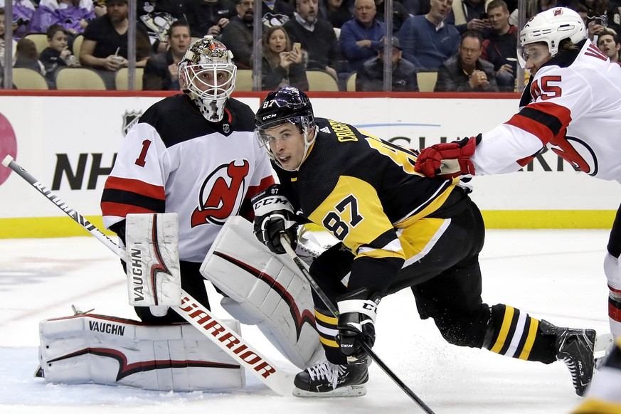 New Jersey Devils' Sami Vatanen (45) checks Pittsburgh Penguins' Sidney Crosby (87) in front of goalie Keith Kinkaid (1) during the second period of an NHL hockey game in Pittsburgh, Monday, Jan. 28, 2019. (AP Photo/Gene J. Puskar)