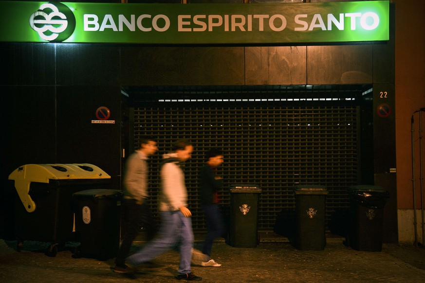 People walk by BES (Espirito Santo Bank) headquarters in Lisbon on August 3, 2014. Portugal is ready to bail out the Banco Espirito Santo (BES) to prevent a catastrophic run on its banks that could plunge its fragile economy further into crisis.AFP PHOTO/ PATRICIA DE MELO MOREIRA