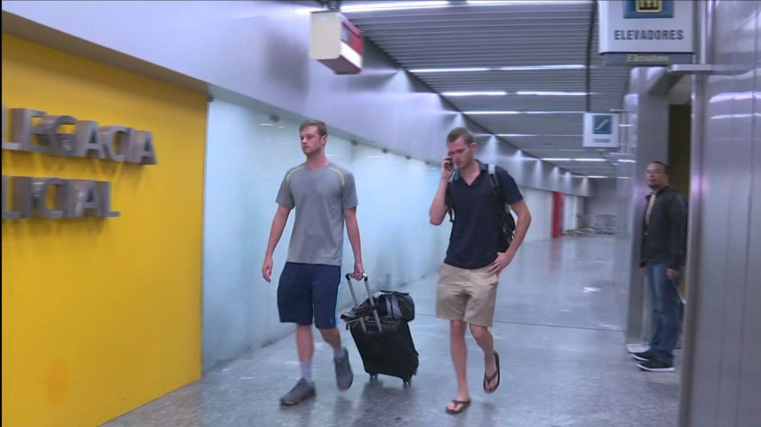 US swimmers Jack Conger (L) and Gunnar Bentz walk into a police office of Rio de Janeiro's international airport after they were stopped from boarding a flight to the United States following their participation in the Rio 2016 Olympic Games, August 17, 2016. REUTERS/Courtesy Globo TV/Handout TPX IMAGES OF THE DAY EDITORIAL USE ONLY