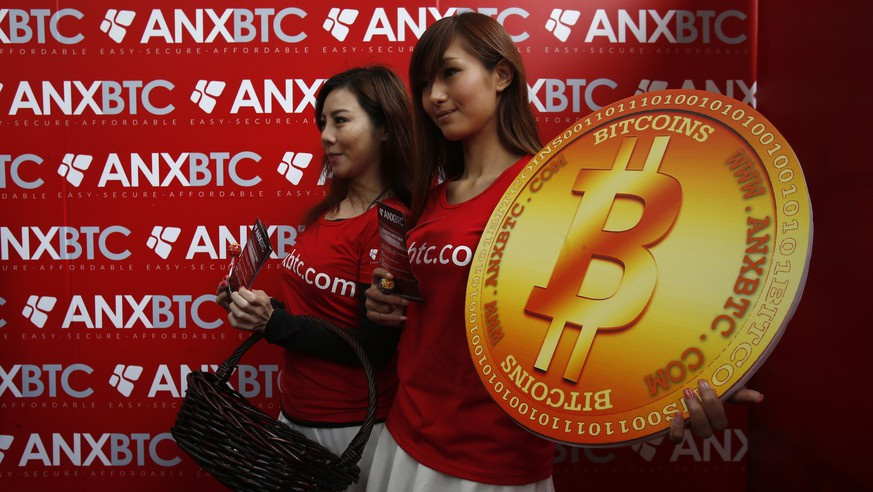 Attendants pose with a bitcoin sign during the opening of Hong Kong's first bitcoin retail store February 28, 2014. REUTERS/Bobby Yip  (CHINA - Tags: BUSINESS)