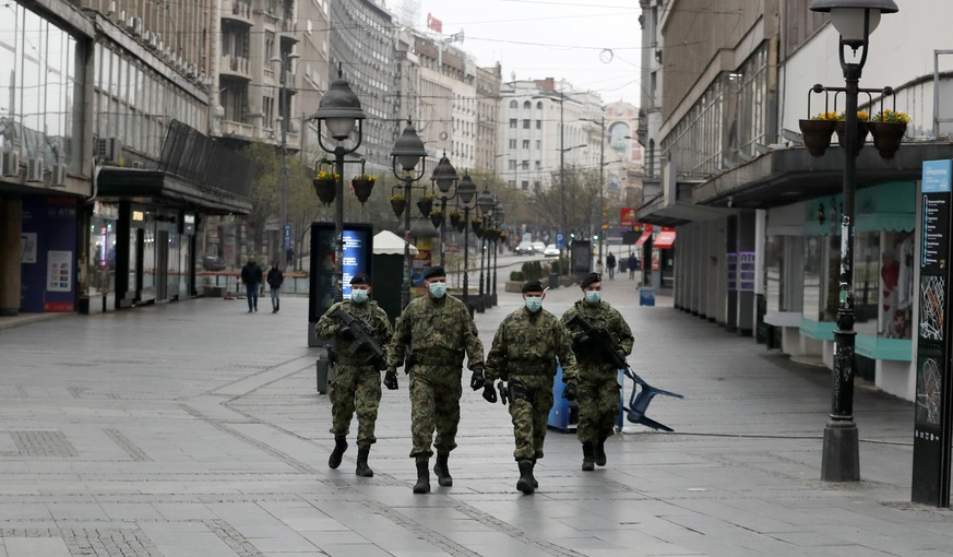 In this March 26, 2020, photo, Serbian army soldiers patrol in Belgrade's main pedestrian street, in Serbia. In the ex-communist Europe and elsewhere, rulers are assuming more power while they introduce harsh measures they say are necessary to halt coronavirus spread. (AP Photo/Darko Vojinovic)