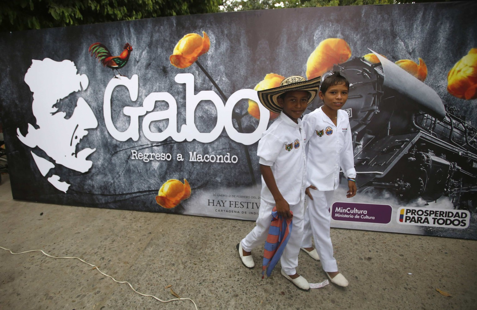 Residents walk next to a poster of Colombian Nobel laureate Gabriel Garcia Marquez, before a symbolic public funeral held for Garcia Marquez, in Aracataca April 21, 2014. Garcia Marquez, 87, who was born in Aracataca, died in Mexico City on April 17, 2014. Colombia is due to hold a separate memorial on Tuesday. REUTERS/John Vizcaino (COLOMBIA - Tags: SOCIETY OBITUARY)