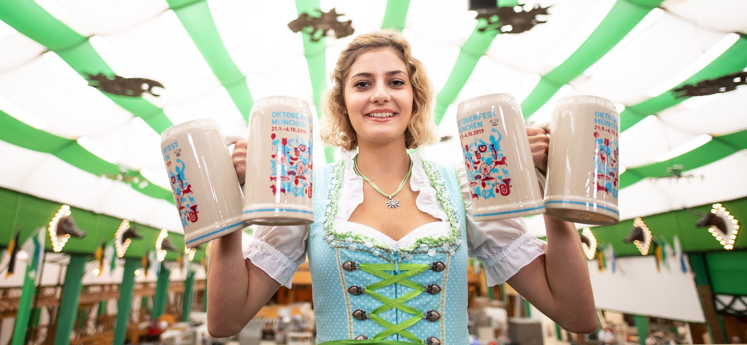 epa07800796 Press attendant Elena poses with the official 2019 Oktoberfest beer mug during a press event on the Theresienwiese fair ground in Munich, Germany, 29 August 2019. The traditional Munich Beer Festival, the world's largest beer festival that annually is visited by people from all over the world, will be held from 21 September to 06 October 2019.  EPA/PHILIPP GUELLAND