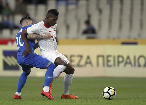 Switzerland's Breel Embolo, right, duels for the ball with Greece's Tasos Donis during an international friendly soccer match between Greece and Switzerland at the Olympic stadium in Athens, Friday, March 23, 2018. (AP Photo/Thanassis Stavrakis)