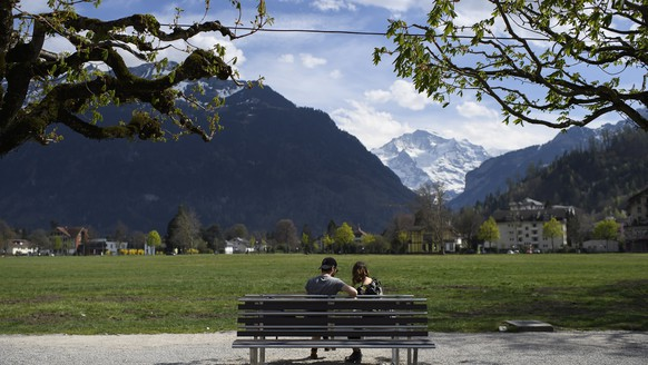 epa08359389 People sit on a bench in the Hoehematte park during the state of emergency of the coronavirus disease (COVID-19) outbreak, in Interlaken, Switzerland, Sunday, April 12, 2020. Countries around the world are taking increased measures to stem the widespread of the SARS-CoV-2 coronavirus, which causes the Covid-19 disease.  EPA/ANTHONY ANEX
