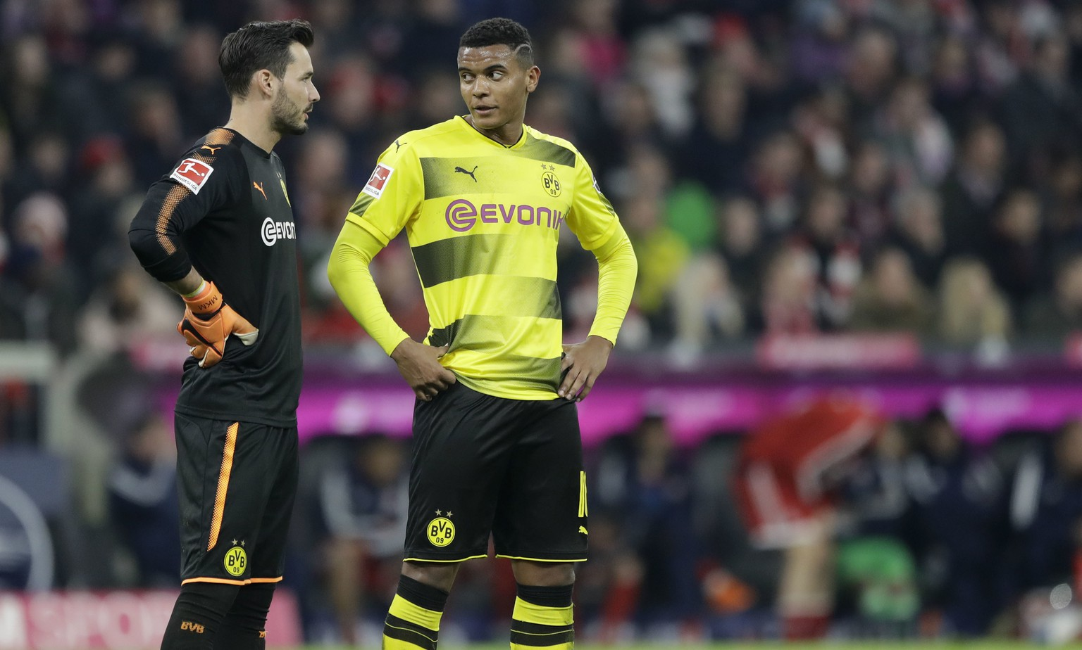 Dortmund goalkeeper Roman Buerki, left, talks to team mate Manuel Akanji during the German Bundesliga soccer match between FC Bayern Munich and Borussia Dortmund in Munich, Germany, Saturday, March 31, 2018. (AP Photo/Matthias Schrader)