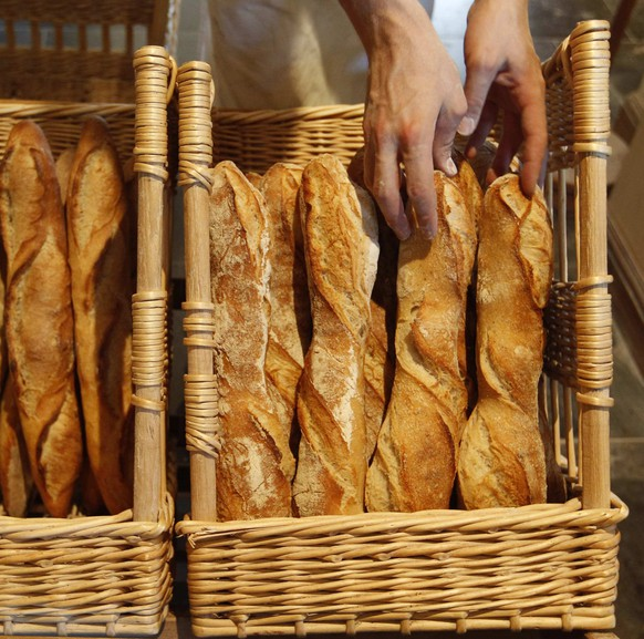 A French baker places freshly-baked baguettes, the traditional French bread, in wicker baskets in his shop in Strasbourg in this August 6, 2010 file picture. In a country known for a statutory 35-hour work week and a generous work-life balance, the