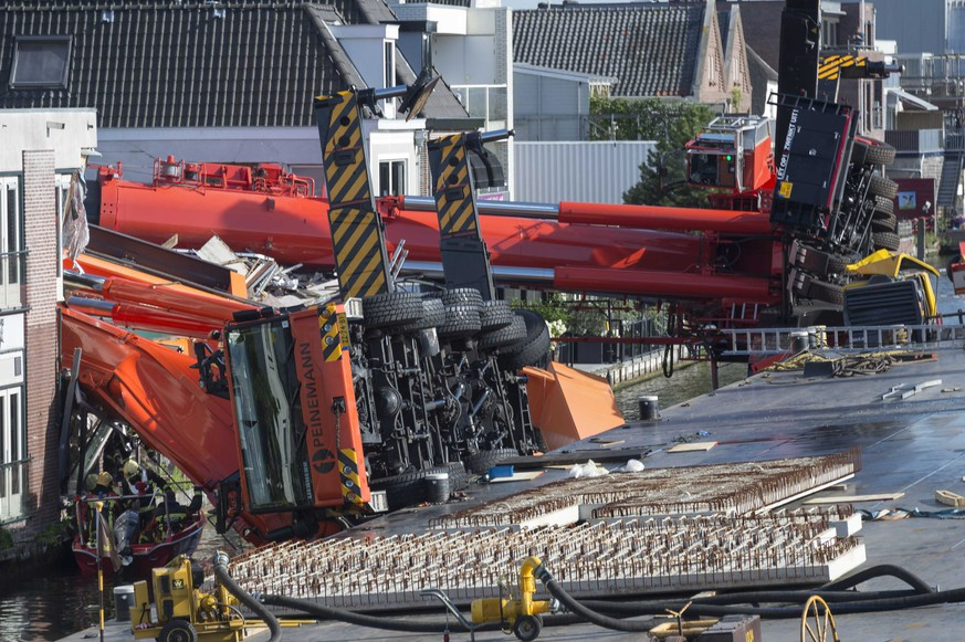 epa04870868 A general view over the site of accident where two cranes fell onto a row of houses in Alphen aan den Rijn, the Netherlands, 03 August, 2015. The cranes were being used to restore a bridge in the city when they tipped over.  EPA/LEX VAN LIESHOUT