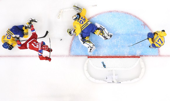 SOCHI, RUSSIA - FEBRUARY 13: Yekaterina Smolentseva #17 of Russia is tripped up while shooting by Erika Grahm #24 of Sweden as Valentina Wallner #35 of Sweden dives to make a save in the second period during the Women's Ice Hockey Preliminary Round Group B game on day six of the Sochi 2014 Winter Olympics at Shayba Arena on February 13, 2014 in Sochi, Russia.  (Photo by Martin Rose/Getty Images)