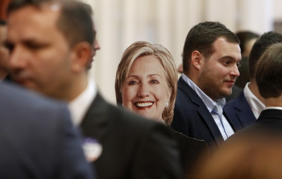 A cardboard cut-out of U.S. presidential candidate Hillary Clinton is displayed between guests at an election night event, organized by the U.S. Embassy in Skopje, Macedonia, Wednesday, Nov. 9, 2016. Donald Trump defeated Clinton to be elected the 45th president of the United States. (AP Photo/Boris Grdanoski)