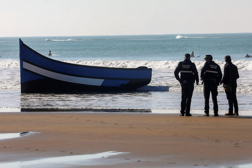 epa07219123 Local policemen stand guard next to a boat in which a total of 30 migrants managed to reach Santa Maria del Mar beach in Cadiz, southern Spain, 09 December 2018. Spanish authorities reported that the police was alerted by residents after all the migrants, from Maghreb, began to run away when they got ashore. The authorities have detained 18 people of them, so far.  EPA/Roman Rios