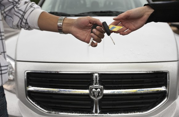 A car salesman hands over a key to a customer at car dealer