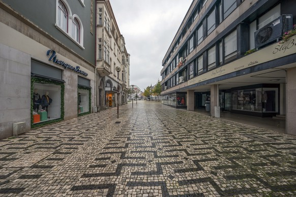 epa08820382 Braga's main shopping streets are deserted during the state of emergency curfew as part of the covid-19 containment measures, Braga, 14 November 2020. With 191 municipalities at risk in Portugal, the government has decreed the closure of all shops and restaurants from 1 pm to 8 am on Saturday and Sunday, in addition to the mandatory confinement for the entire population of municipalities at risk.  EPA/HUGO DELGADO
