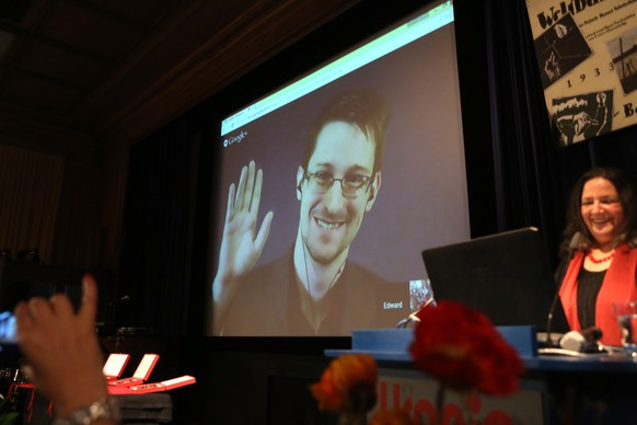 BERLIN, GERMANY - DECEMBER 14:  Former National Security Agency (NSA) contractor turned whistleblower Edward Snowden waves during a video conference at an award ceremony for the Carl von Ossietzky journalism prize on December 14, 2014 in Berlin, Germany. Filmmaker Laura Poitras, Snowden and journalist Glenn Greenwald (the latter two in absentia) were awarded the prize by the International League for Human Rights for having 'put their personal freedom on the line to expose abuse of power' by Germany and the United States in their revelations of the extent of government surveillance on ordinary citizens in the name of 'national security' in the wake of terrorist attacks. The prize is named for journalist and Nobel Peace Prize winner Ossietzky, who died from complications from being held as a dissident in a Nazi concentration camp. A bid to allow Snowden, who has temporary asylum in Moscow, to testify in Berlin before an NSA parliamentary inquiry is ongoing.  (Photo by Adam Berry/Getty Images)