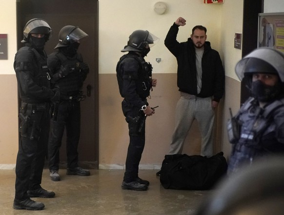 Rap singer Pablo Hasél reacts next to police officers before being detained at the University of Lleida, Spain, Tuesday, Feb. 16, 2021. A rapper in Spain and dozens of his supporters have locked themselves inside a university building in the artist's latest attempt to avoid a prison sentence for insulting the monarchy and praising terrorism. (AP Photo/Joan Mateu)