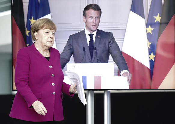 German Chancellor Angela Merkel arrives for a news conference with French President Emmanuel Macron, connected by video, after a joint video conference in Berlin, Germany, Monday, May 18, 2020. One topic was the corona pandemic and its consequences. (Kay Nietfeld/dpa via AP)