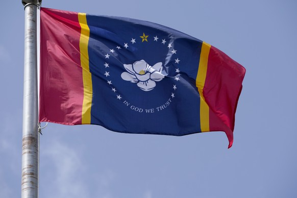 The magnolia centered banner chosen Wednesday, Sept. 2, 2020 by the Mississippi State Flag Commission flies outside the Old State Capitol Museum in downtown Jackson, Miss. The nine member committee voted to recommend a design with the state flower. That design will go on the November ballot for voters consideration and if approved, it will become the new state flag. (AP Photo/Rogelio V. Solis)