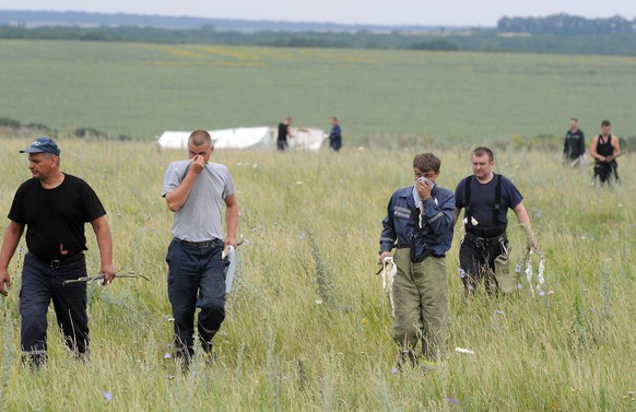 People search for bodies on July 18, 2014 at the site of the crash of a Malaysian airliner carrying 298 people from Amsterdam to Kuala Lumpur, near the town of Shaktarsk, in rebel-held east Ukraine. Pro-Russian separatists in the region and officials in Kiev blamed each other for the crash, after the plane was apparently hit by a surface-to-air missile. All 298 people on board Flight MH17 died when the plane crashed. Rescue workers at the crash site said that they had found one of the black boxes from the passenger liner. AFP PHOTO/DOMINIQUE FAGET