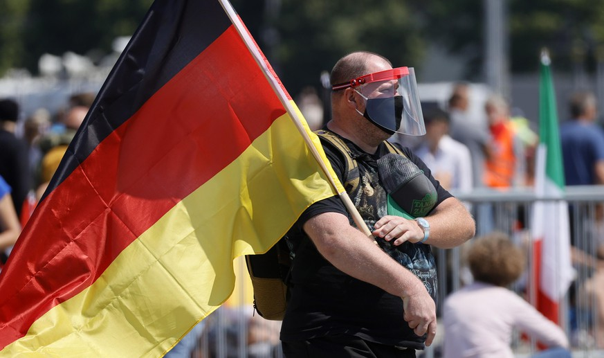 epa08426051 A man hold a German flag during a demonstration of the initiative 'Lateral thinking' in Stuttgart, Germany, 16 May 2020. The demonstration is directed against the Coronavirus restrictions and for basic rights such as freedom of assembly and freedom of religion.  EPA/RONALD WITTEK