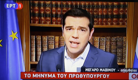 In this photo taken from television Greece's Prime Minister Alexis Tsirpas delivers a televised address to the nation from his office at Maximos Mansion in Athens, Wednesday, July 1, 2015. Tsipras has vowed to push on with his plan for a referendum this Sunday on the recent proposals from the country's creditors. The banner reads ''The statement of the Prime Minister.'' (AP Photo/Thanassis Stavrakis)