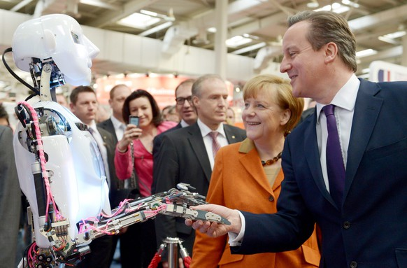epa04118732 A handout picture provided by the Deutsche Messe AG shows German Chancellor Angela Merkel (2-R) and British Premier David Cameron holding the hand of a humanoid robot during their opening tour across the CeBIT fair in Hanover, Germany, 10 March 2014. The world's largest computer expo runs from 10 to 14 March 2014. Britain is the official partner country of this year's CeBIT.  EPA/RAINER JENSEN / DEUTSCHE MESSE AG / HANDOUT MANDATORY CREDIT. HANDOUT EDITORIAL USE ONLY/NO SALES