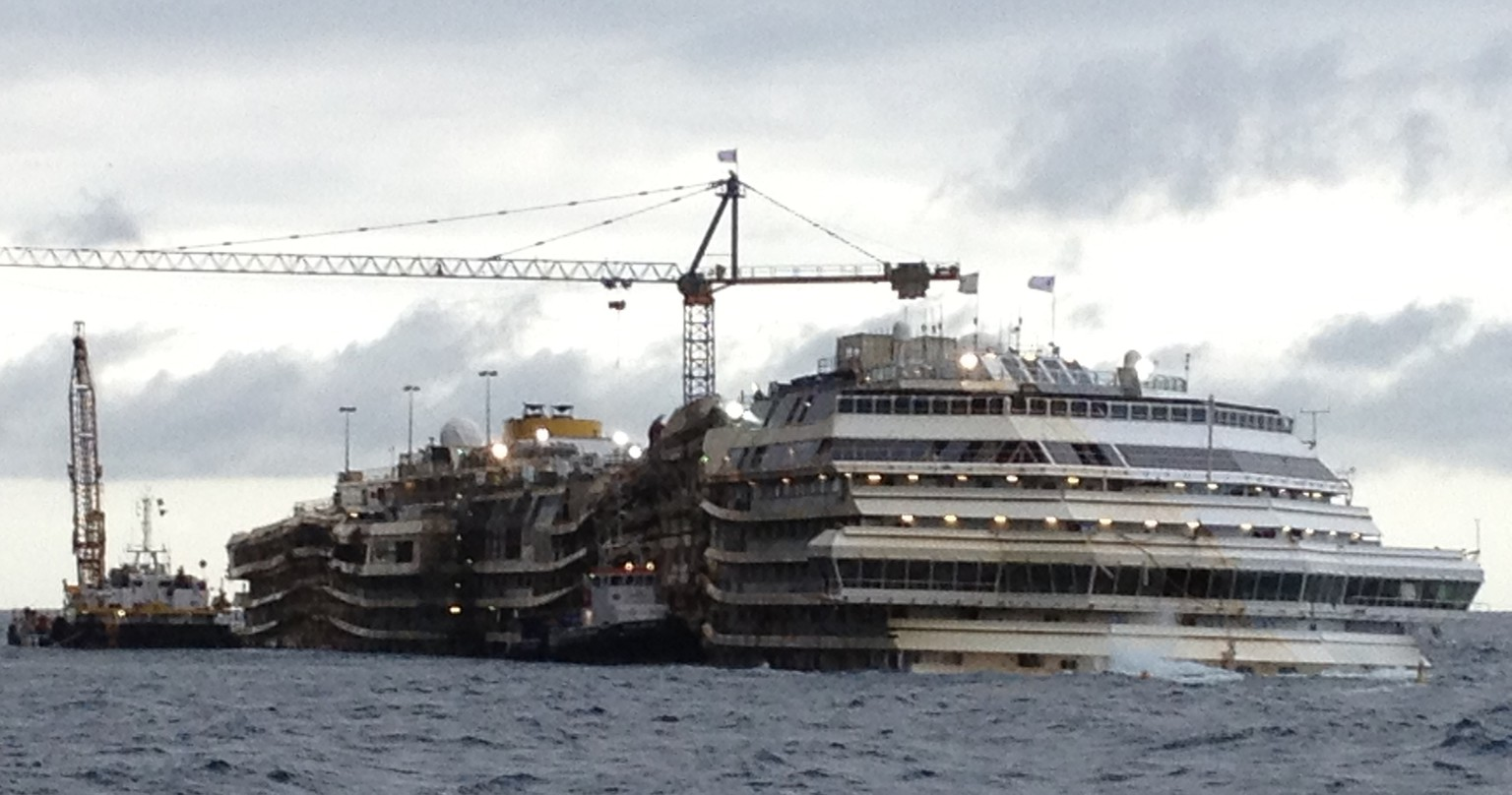 FILE -- In this file photo taken on Jan. 23, 2014, the Costa Concordia cruise liner lies in the waters of the Giglio Island, Italy. The last major stage of work has begun to ready the shipwrecked Costa Concordia cruise liner for removal to land for scrapping. On Monday, April 28, 2014, a first tank — the biggest and heaviest of 19 — was fastened to the starboard side. The tanks will be filled with water to help stabilize the Concordia, now resting on an artificial seabed after a daring engineering operation set it upright in September. Eventually, the tanks will be drained and function like giant water wings to help float away the Concordia. (AP Photo/Luigi Navarra)