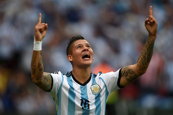 """(Files) In this file picture taken on June 25, 2014, Argentina's defender Marcos Rojo celebrates his goal during a Group F football match against Nigeria at the Beira-Rio Stadium in Porto Alegre during the 2014 FIFA World Cup. A tweet published from Manchester United's official account on Tuesday evening stated that it """"has reached agreement with Sporting Lisbon to sign defender Marcos Rojo, subject to a medical and personal terms"""".  AFP PHOTO / PEDRO UGARTE"""