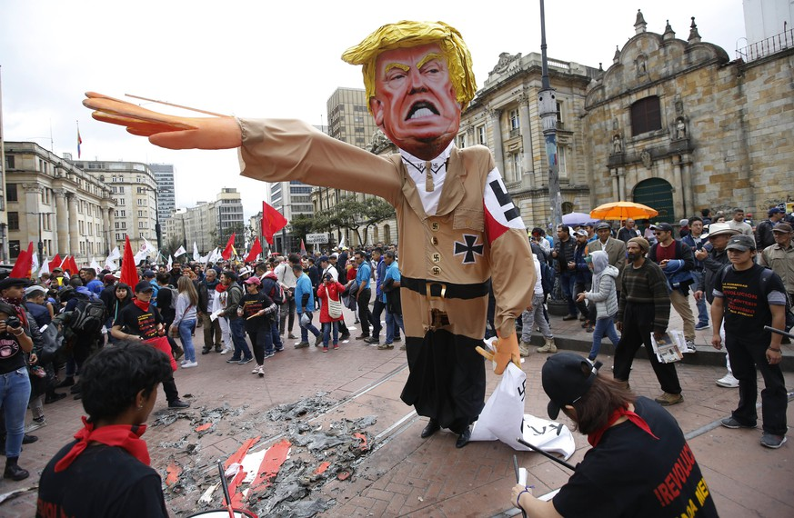 In this May 1, 2018 photo, protesters prepare to set fire to an effigy depicting U.S. President Donald Trump dressed in a Nazi uniform, during a demonstration marking May Day to honor workers, in Bogota, Colombia. (AP Photo/Fernando Vergara)