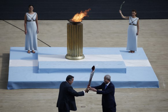 epaselect epa09532029 Hellenic Olympic Committee president and International Olympic Committee (IOC) member Spyros Capralos (L) passes the Olympic Torch to Yu Zaiqing (R), vice president of the Chinese Olympic Committee, during the handover ceremony of the Olympic Flame for the Beijing 2022 Winter Olympics at the Panathenaic Stadium in Athens, Greece, 19 October 2021.  EPA/YANNIS KOLESIDIS