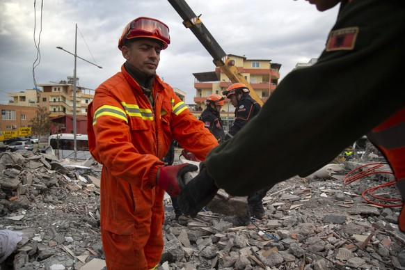 In this photo taken on Thursday, Nov. 28, 2019, rescuers from Turkey search with their Albanian colleagues at a collapsed building after the 6.4-magnitude earthquake in Durres, western Albania.In the initial hours after a deadly pre-dawn earthquake struck Albania, pancaking buildings and trapping dozens of sleeping people beneath the rubble, the country's neighbors sprang into action. Offers of help flooded in from across Europe and beyond, with even traditional foes setting aside their differences in the face of the natural disaster. The 6.4-magnitude earthquake that struck Albania on Tuesday killed at least 49 people, injured 2,000 and left at least 4,000 homeless. (AP Photo/Visar Kryeziu)