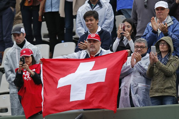 Fans holding the Swiss flag cheer as Switzerland's Stan Wawrinka wins his fourth round match of the French Open tennis tournament against France's Gilles Simon in three sets, 6-1, 6-4, 6-2, at the Roland Garros stadium, in Paris, France, Sunday, May 31, 2015. (AP Photo/Michel Euler)