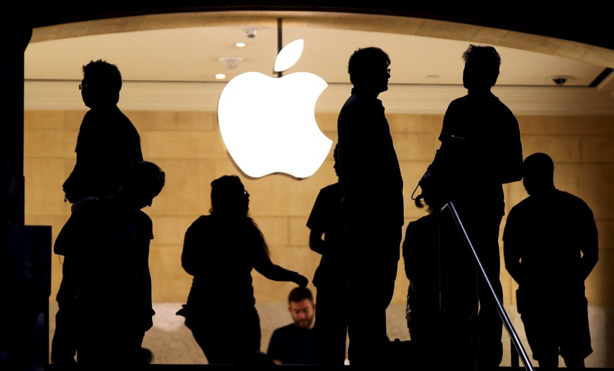 Customers stand beneath an Apple logo at the Apple store in Grand Central station in New York City, July 21, 2015. U.S. stocks opened lower on Tuesday as the dollar remained at a three-month high and ahead of a host of earnings from technology giants including Apple, Microsoft and Yahoo.  REUTERS/Mike Segar