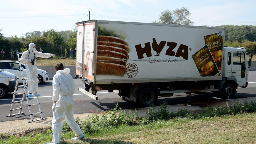 JAHRESRUECKBLICK 2015 - AUGUST - Forensic experts investigate a truck in which refugees were found dead as it stands on freeway autobahn A4 between Parndorf and Neusiedl, Austria, 27 August 2015. According to reports, some 50 refugees were found dead in the lorry parked at the autobahn. It cannot be confirmed if the dead suffocated in the truck, as some media have reported. The lorry was discovered by highway workers who called police. The driver has disappeared, according to media reports. (KEYSTONE/EPA/ROLAND SCHLAGER)